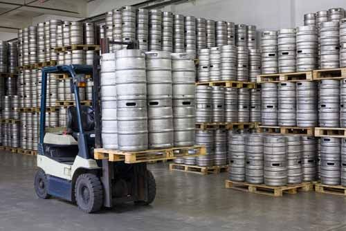 Barrels of beer are stored in a warehouse