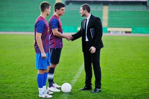An Athlete Agent shakes hands with soccer players on a soccer field.
