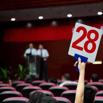 An audience member holds up an auction number while bidding at an auction.