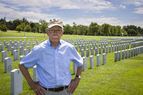 A veteran stands in front of a veteran cemetery
