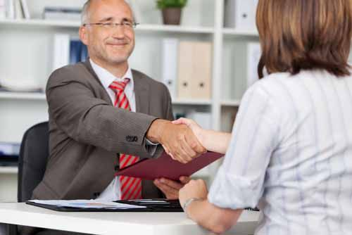 Two adults shake hands over a Fiduciary agreement