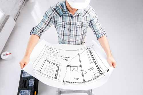 A contractor looks at blueprints