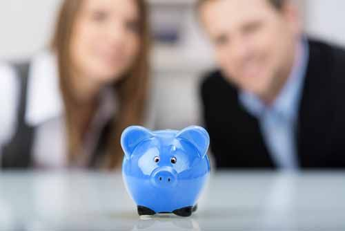 A couple looks at a piggy bank