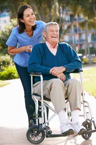 A Caregiver Helps a Patient in a Wheelchair