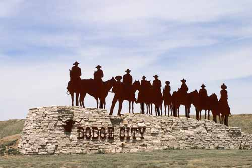 Cowboys on horses are on top of a 'Dodge City' sign in Kansas