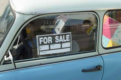 An old car has a 'For Sale' sign in the window
