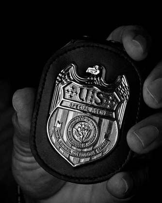 A hand holds a private detective badge