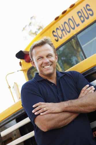 A school bus driver stands in front of a school bus.