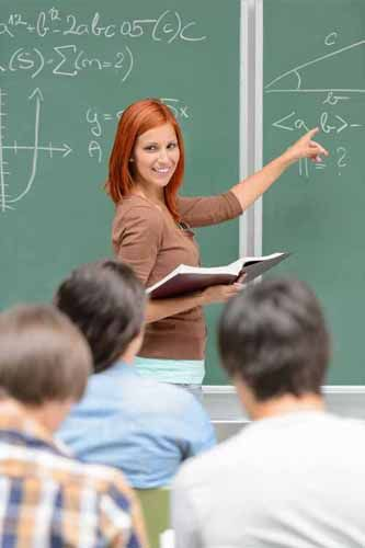 A Postsecondary teacher points to a chalkboard in front of a class