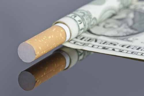 A dollar bill is wrapped around a cigarette
