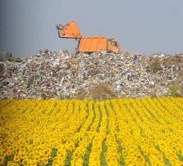 A truck dumps trash in a landfill.