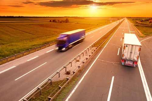 Two Freight Broker trucks pass each other on a highway