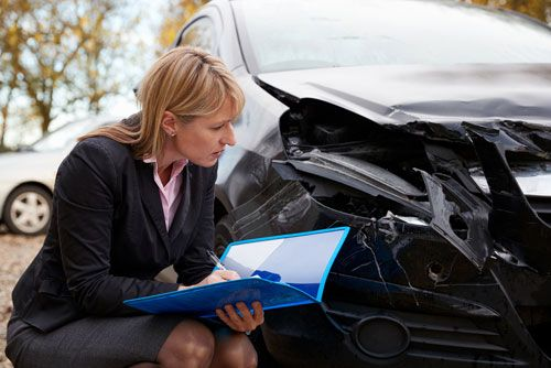 A Tennessee Public Adjuster examines damage to a car