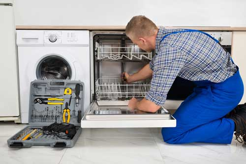 A service provider works on a dishwasher