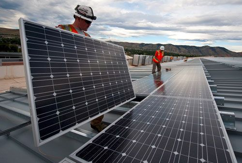 Workers install a solar energy system