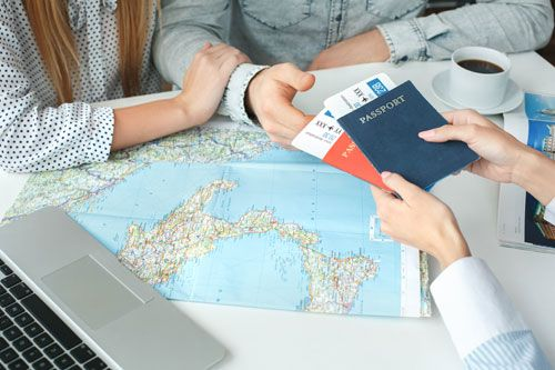 A travel agent hands airline tickets to clients