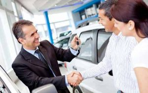 A car dealer hands keys to a customer.