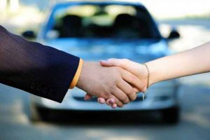 A car dealer shakes hands with a client.