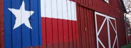 A barn in Texas with the state flag.