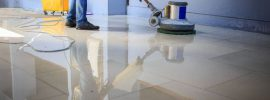 A janitorial worker cleans a floor.