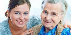 A young woman and elderly woman smile.