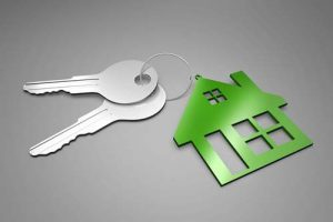 A house-shaped keychain holds a set of house keys.