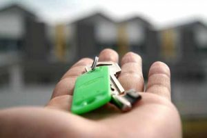 A hand holds keys with houses in the background.